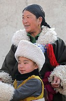 China, Qinghai, Amdo, Tongren Rebkong, Monastery of Gomar Guomari Si, Losar New Year festival, Mother an child in full attire