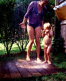 Mother and her naked son rinsing under an outdoor shower