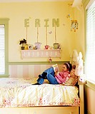 A small girl is reading a book in the bedroom