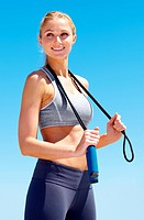 An attractive young woman standing upright and holding a skipping rope over her shoulders