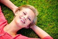 Portrait of a beautiful young blonde lying on the grass smiling _ Copyspace