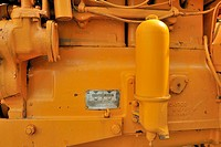 A close up view of part of the gasoline combustion engine ane serial number plate on an antique 1952 Minneapolis Moline farm tractor.