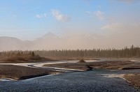 A landscape image of a sand storm blowing off the sand flats on the Athabasca river in Jasper National Park