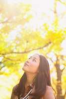 Japanese woman with long hair looking up with yellow leaves in the background