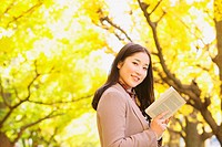 Japanese woman with long hair looking at camera while holding a book with yellow leaves in the background
