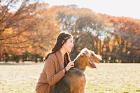 Japanese woman with long hair and a dog in a park looking away