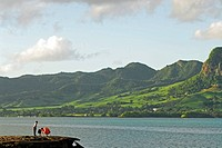 Mauritius, Mahebourg, man with young children fishing and a scenic view of lush mountain range in the background