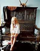 A small girl is sitting on a large wooden bench in the house