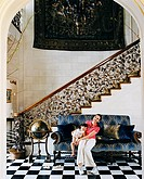Mother and Daughter on Sofa by Staircase with Ornate Railing