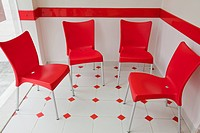 Four red chairs inside a Western pizza restaurant.