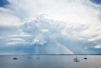 Sailboats, rainbow and storm clouds
