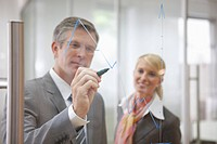 Mature businessman drawing diagram on glass in office