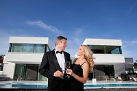 Mature couple holding glasses of champagne in front of modern luxury home