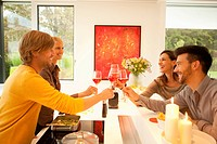 Four friends toasting glasses in kitchen