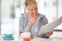 Young woman reading newspaper over breakfast