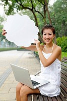 Young Asian woman with thought bubble using laptop