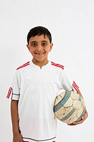 Young Asian boy wearing football kit