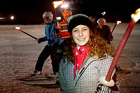 Girl holding flaming torch on ski slope at night, portrait