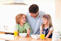Smiling father with his children having breakfast
