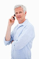 Portrait of a mature man making a phone call while looking at the camera