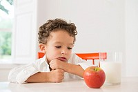Four year old boy with milk and fruit for beakfast