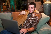 Young male on couch with cat and laptop