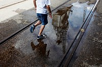 A boy running along Harbourside with a crane reflected in a puddle