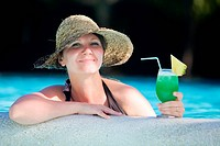 Girl relaxing in swimming pool with glass of tropical drink