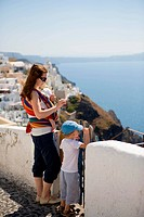Family trip to Europe. Young mother with two kids exploring Greek town.