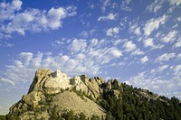 White puffy clouds behind Presidents George Washington, Thomas Jefferson, Teddy Roosevelt and Abraham Lincoln at Mount Rushmore National Memorial, Sou...