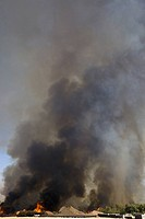 Brush fire in desert emitting large black plumes of smoke, east of Needles in Arizona