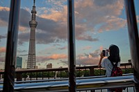 Girl taking pictures Sky Tree from Sumidagawa river, Asakusa District, Tokyo, Japan