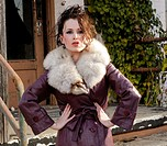 A 24 year old brunette woman looking at the camera wearing an overcoat with a faux fur color in a run-down urban setting