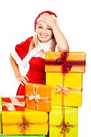 Young beautiful blond happy smiling woman in Santa costume surrounded by Christmas gift boxes, isolated on white background