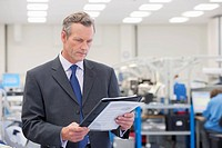 Businessman reviewing paperwork in manufacturing plant