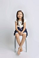 Young girl posing on chair with white background