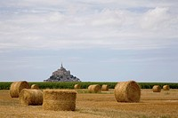 France, Normandy, distant view of Mont St. Michel across field with hay bales