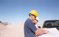 Workers Reading Plans on Car