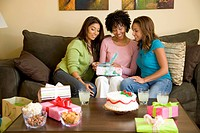 Three women sitting on sofa and looking at gift box