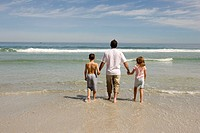 Father, son and daughter walking on the beach.