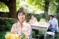 Girl has plate in garden,portrait