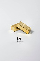 Businessman standing in front of gold bar on white background