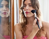 young woman doing her make_up