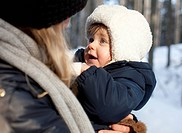 woman holding babygirl in winter clothes