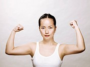 Young asian woman flexing her muscles