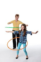 Caucasian mother and daughter twirling plastic hoops