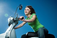 Close_up of a teenage girl riding a scooter