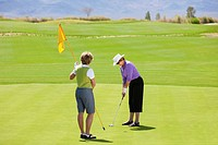 Senior woman putts on green