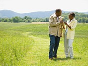 Senior man and a senior woman walking in a field