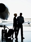 Profile of a businesswoman and a businessman walking with suitcases by an airplane